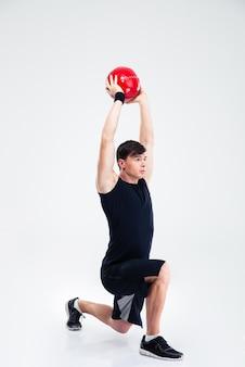 Volledig lengteportret van atletische mensentraining met geïsoleerde geschiktheidsbal