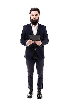 Volledig lengteportret van bebaarde zakenman met tablet in handen, dat op witte achtergrond wordt geïsoleerd