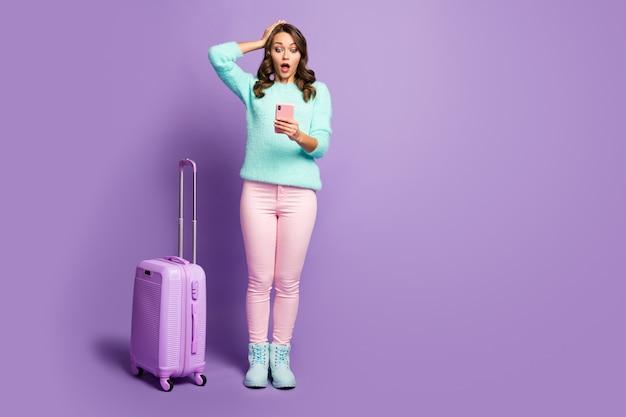 Volledig lengteportret van boos dame gemiste vluchtregistratie hand op hoofd rollende koffer kijktijd telefoon slijtage fuzzy sweater pastel roze broek schoenen.