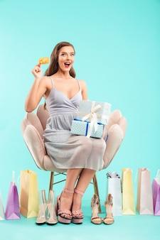 Volledig lengteportret van brunette shopper vrouw zittend op een fauteuil tijdens het kiezen van meisjesachtige sandalen en kopen met creditcard, geïsoleerd over blauwe muur