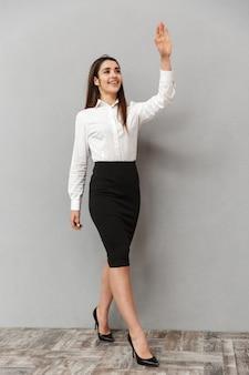 Volledig lengteportret van brunette zakenvrouw 20s in wit overhemd en zwarte rok wandelen met glimlach en groet met zwaaiende hand, geïsoleerd over grijze muur