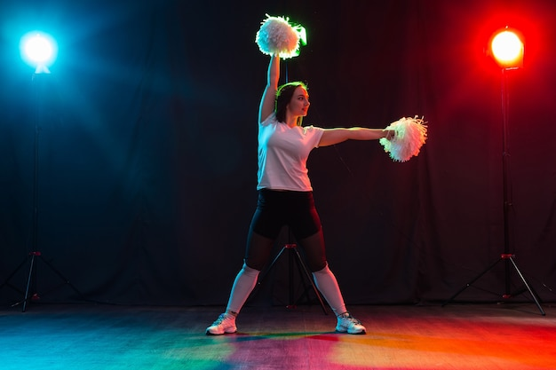 Volledig lengteportret van cheerleader die met pom-poms danst.