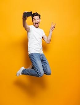 Volledig lengteportret van de blije mens met bruin haar die en vredesteken springen tonen terwijl het nemen van selfie op zwarte smartphone