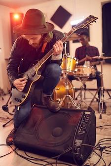 Volledig lengteportret van de eigentijdse jonge mens die elektrische gitaarsolo speelt