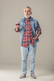 Volledig lengteportret van de gebaarde modieuze rijpe mens in jeans.
