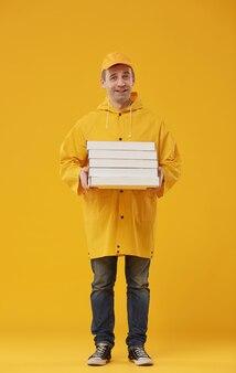 Volledig lengteportret van de volwassen de holdingspizzadozen van de leveringsmens