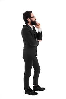 Volledig lengteportret van denken bebaarde zakenman, dat op witte achtergrond wordt geïsoleerd