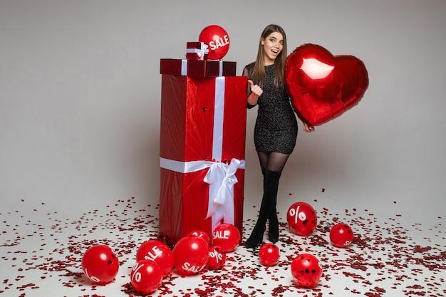 Volledig lengteportret van donkerbruin kaukasisch meisje met hartvormige ballon die met haar duim op verpakte cadeautjes richt. luchtballonnen met verkoop- en kortingsbord op de vloer met confetti.