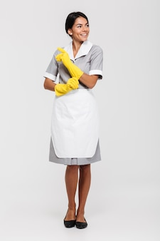 Volledig lengteportret van een aantrekkelijke glimlachende huishoudster