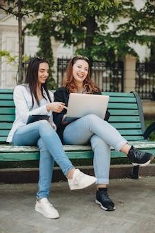 Volledig lengteportret van een aantrekkelijke kaukasische vrouwenzitting op een bank die op een laptopscherm richt terwijl haar vriend omhoog lachend buiten kijkt.