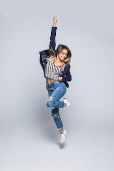 Volledig lengteportret van een blije jonge vrouw die en over grijze muur springt viert
