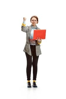 Volledig lengteportret van een boos vrouwelijk notitieboekje dat van de studentenholding op witte ruimte wordt geïsoleerd