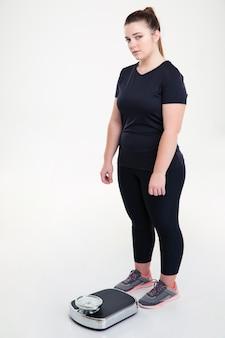 Volledig lengteportret van een dikke vrouw die zich met een weegmachine bevindt die op een witte muur wordt geïsoleerd
