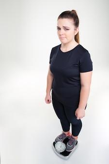Volledig lengteportret van een droevige dikke vrouw die zich op een weegmachine bevindt die op een witte muur wordt geïsoleerd