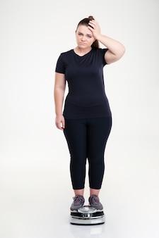 Volledig lengteportret van een droevige dikke vrouw die zich op weegmachine bevindt die op een witte muur wordt geïsoleerd