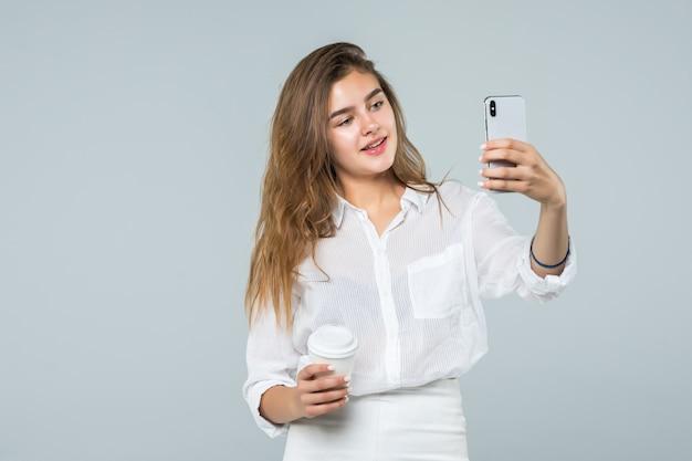 Volledig lengteportret van een gelukkig glimlachend meisje die mobiele telefoon met behulp van terwijl status en koffiekop over witte achtergrond houden