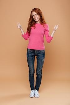 Volledig lengteportret van een gelukkig glimlachend roodharigemeisje met omhoog duimen