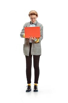 Volledig lengteportret van een gelukkig het glimlachen vrouwelijk die notitieboekje van de studentenholding op witte ruimte wordt geïsoleerd