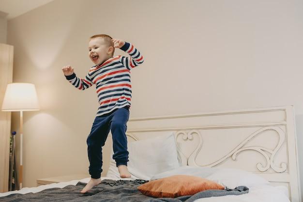 Volledig lengteportret van een gelukkig jong geitje dat op het bed in de ochtend springt die thuis gelukkig tong toont.