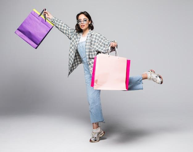 Volledig lengteportret van een gelukkig mooi meisje die boodschappentassen houden tijdens het rennen en geïsoleerd kijken