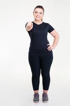Volledig lengteportret van een gelukkige dikke vrouw in sportkleding die met de vinger wijst geïsoleerd op een witte muur