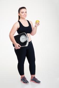 Volledig lengteportret van een gelukkige dikke vrouw met een weegmachine en appel geïsoleerd op een witte muur