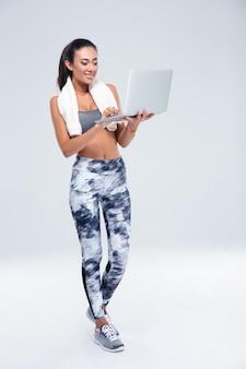 Volledig lengteportret van een gelukkige geschiktheidsvrouw die laptop met behulp van die op een witte muur wordt geïsoleerd