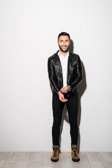 Volledig lengteportret van een gelukkige jonge man in jasje