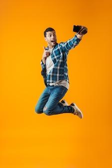 Volledig lengteportret van een gelukkige jonge mens die geruite overhemd draagt ?? dat over oranje achtergrond wordt geïsoleerd, springt, neemt een selfie