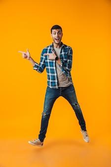 Volledig lengteportret van een gelukkige jonge mens die geruite overhemd draagt dat over oranje muur wordt geïsoleerd, het lopen, weg richt