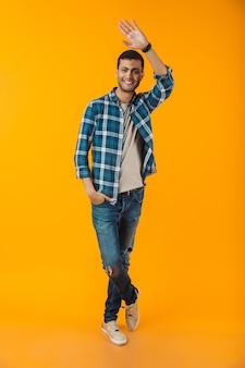 Volledig lengteportret van een gelukkige jonge mens die plaidoverhemd draagt dat over oranje muur, golvende hand wordt geïsoleerd