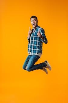 Volledig lengteportret van een gelukkige jonge mens die plaidoverhemd draagt dat over oranje muur wordt geïsoleerd, die het vieren van succes springt