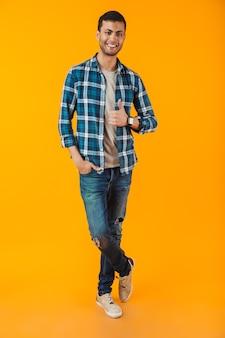 Volledig lengteportret van een gelukkige jonge mens die plaidoverhemd draagt dat over oranje muur wordt geïsoleerd, duimen omhoog