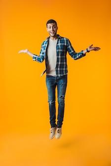 Volledig lengteportret van een gelukkige jonge mens die plaidoverhemd draagt dat over oranje muur wordt geïsoleerd, het vieren
