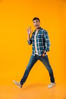 Volledig lengteportret van een gelukkige jonge mens die plaidoverhemd draagt dat over oranje muur wordt geïsoleerd, lopende, golvende hand