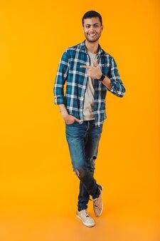 Volledig lengteportret van een gelukkige jonge mens die plaidoverhemd draagt dat over oranje muur wordt geïsoleerd, wijzende vinger weg