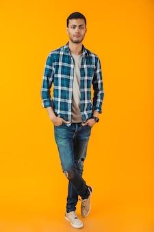 Volledig lengteportret van een gelukkige jonge mens die plaidoverhemd draagt dat over oranje muur wordt geïsoleerd