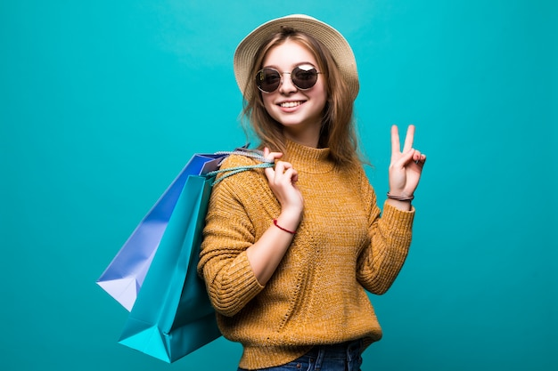 Volledig lengteportret van een gelukkige opgewekte vrouw die in heldere kleurrijke kleren het winkelen zakken houden terwijl status en vredesgebaar tonen dat op groene muur wordt geïsoleerd