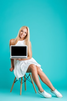 Volledig lengteportret van een gelukkige, vrolijke vrouw die op een stoel zit en een laptop met een leeg scherm toont die op de blauwe achtergrond wordt geïsoleerd