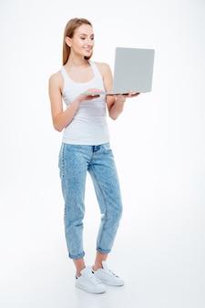 Volledig lengteportret van een gelukkige vrouw die laptop computer met behulp van die op een witte achtergrond wordt geïsoleerd