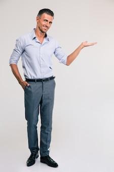 Volledig lengteportret van een gelukkige zakenman die copyspace op de palm houdt over grijze ruimte