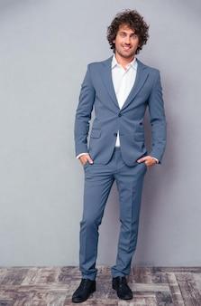 Volledig lengteportret van een gelukkige zakenman die zich op grijze muur bevindt en voorzijde bekijkt
