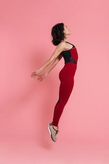Volledig lengteportret van een geschikte mooie sportenvrouw die oefeningen doet die over roze muur worden geïsoleerd, springend