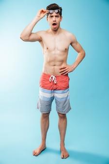 Volledig lengteportret van een geschokte jonge shirtless mens