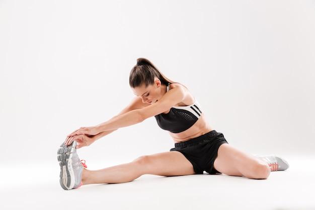 Volledig lengteportret van een gezonde gemotiveerde sportvrouw uitrekkende spieren