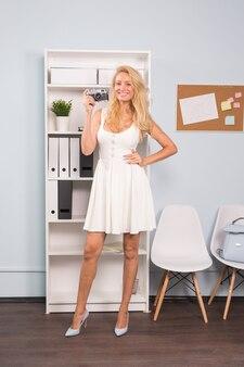 Volledig lengteportret van een glimlachend mooi meisje in kleding die foto op een retro camera in coworking nemen