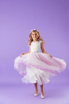 Volledig lengteportret van een glimlachend vrolijk mooi meisje gekleed in een prinsessenjurk die over violette muur wordt geïsoleerd, dansen