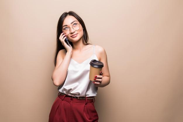 Volledig lengteportret van een glimlachende aziatische mobiele telefoon van de vrouwenbespreking terwijl het houden van kop van koffie geïsoleerd over beige muur gaan