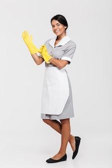Volledig lengteportret van een glimlachende jonge huishoudster