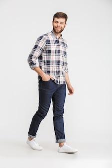 Volledig lengteportret van een glimlachende jonge mens in plaidoverhemd